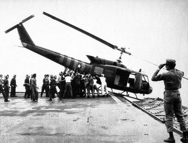 Zeemacht-personeel aan boord van de USS Blue Ridge duwt een Huey-helikopter overboord - 29 april 1975